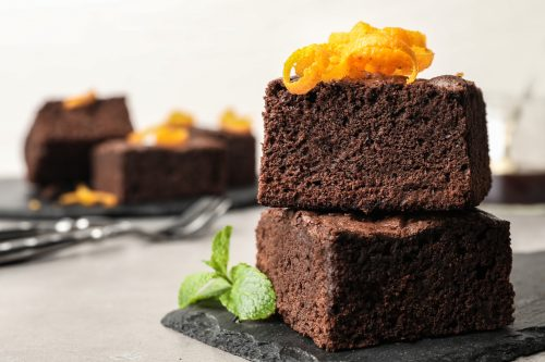 Fresh brownies decorated with orange peel and mint on table, space for text. Delicious chocolate pie
