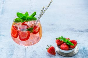 Strawberry Gin Smash Cocktail with two straws topped with fresh mint and served with a bowl of strawberries