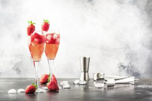 Sparkling Berry Cocktail Flutes accompanied by crushed ice and strawberries